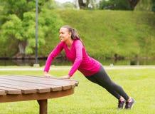 做在长凳的微笑的妇女俯卧撑户外 免版税库存照片