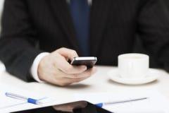 与智能手机读书新闻的商人 免版税库存照片