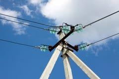 在蓝天的电源线支柱与白色云彩 免版税库存照片