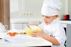 切开品尝他的面团混合物的小厨师 库存图片