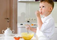 切开品尝他的面团混合物的小厨师 免版税库存照片