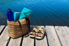 海滩袋子和书在湖 库存图片