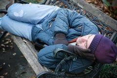 在公园长椅的无家可归者 免版税库存照片