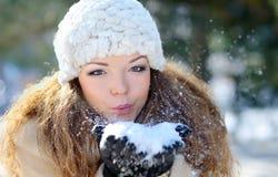 佩带温暖的冬天衣裳和帽子吹的雪的女孩 免版税库存照片