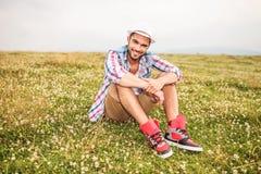 坐在草和花的领域的偶然人 免版税库存照片