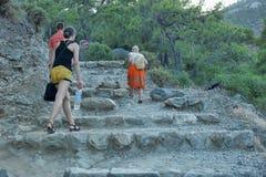 Οι τουρίστες αναρριχούνται στα βήματα πετρών που χαράζονται στο βράχο Στοκ εικόνα με δικαίωμα ελεύθερης χρήσης
