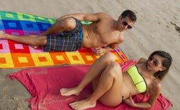 在海洋海滩的年轻夫妇谎言 免版税库存图片
