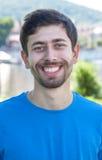 有胡子和蓝色衬衣的可爱的人是愉快的 图库摄影
