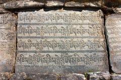 玛尼墙壁和石头与佛教标志 免版税库存照片