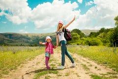 母亲和女儿在路走通过领域 免版税库存照片