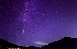 Фиолетовые звезды ночного неба Млечный путь через горы Стоковое Изображение
