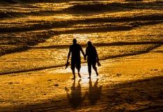 走的夫妇拿着手海滩 免版税图库摄影