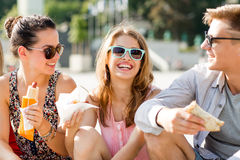 小组微笑的朋友坐城市广场 免版税库存照片