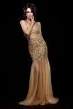 高雅 金黄长的礼服的贵族夫人在黑背景 免版税库存图片
