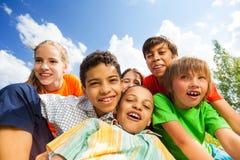 坐在拥抱的愉快的微笑的孩子关闭得外面 免版税库存图片
