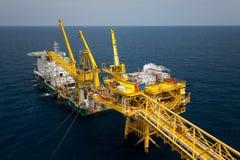 闯入在近海的设施平台油和煤气产业,供应小船或驳船工作的支持工作者在近海平台 图库摄影