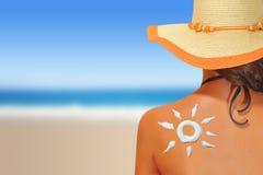 有太阳形状的遮光剂的妇女 免版税库存照片