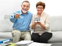 拿着一个小屋的愉快的资深夫妇 免版税库存照片