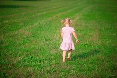 跑在草草甸的逗人喜爱的小女孩 免版税库存图片