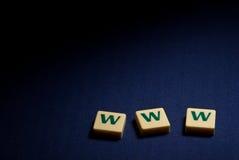 在蓝色背景的万维网万维网塑料字母符号 免版税库存图片