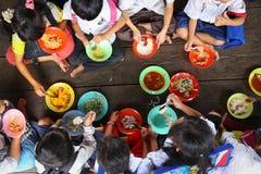 Παιδιά που έχουν το μεσημεριανό γεύμα στο ασιατικό σχολείο Στοκ Εικόνα