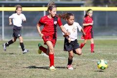 女孩青年足球跑为球的足球运动员 免版税库存图片