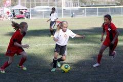 女孩青年足球跑为球的足球运动员 图库摄影