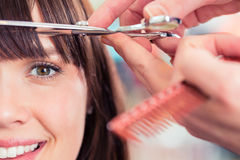 Женщина вырезывания парикмахера грохает волосы Стоковое Изображение RF