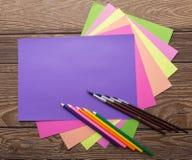 Σχολικά χαρτικά: άνετο έγγραφο χρωμάτων και μολύβι και βούρτσα στο ξύλινο υπόβαθρο Στοκ Εικόνες