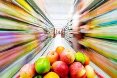 超级市场内部,充满购物车果子  库存照片