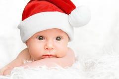 圣诞节帽子的逗人喜爱的新出生的婴孩 免版税图库摄影