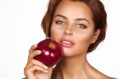 Το νέο όμορφο προκλητικό κορίτσι με τη σκοτεινή σγουρή τρίχα, τους γυμνούς ώμους και το λαιμό, που κρατούν το μεγάλο κόκκινο μήλο Στοκ Φωτογραφίες