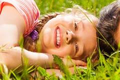 关闭的愉快的女孩放置在绿草的观点 库存照片