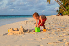 Замок песка здания ребенка на пляже захода солнца Стоковые Фотографии RF