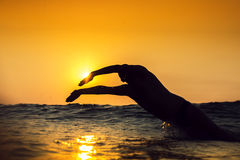 日出,年轻人游泳在海 免版税图库摄影