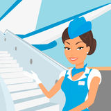 佩带蓝色衣服和飞机的女性空中小姐 免版税库存照片