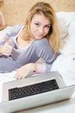 赞许:获得美丽的白肤金发的年轻的女商人或的学生特写镜头画象运作从在便携式计算机上的家的乐趣 库存图片