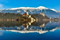 在海岛上的教会在有山风景的湖 免版税库存照片