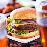 与啤酒杯和鸡翼的汉堡 免版税图库摄影