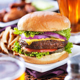 乳酪汉堡用啤酒和炸薯条关闭  免版税图库摄影