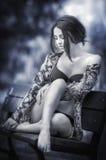 泳装坐的可爱的女孩在长凳放松了 与摆在公园的浪漫看起来的时兴的女性模型 美丽的女孩 免版税库存图片