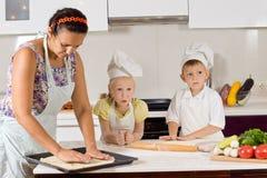 做食物的母亲帮助的厨师孩子 免版税库存图片