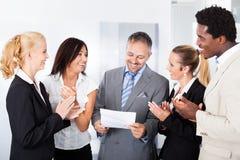 Счастливые предприниматели аплодируя бизнесмену Стоковые Изображения