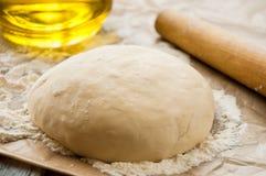 Ξύλινη κυλώντας καρφίτσα με την πρόσφατα έτοιμη ζύμη για την πίτσα Στοκ Εικόνες