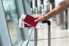Крупный план человека держа пасспорты и посадочный талон Стоковая Фотография