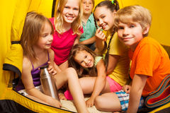 坐在帐篷的六个好孩子、男孩和女孩 免版税图库摄影