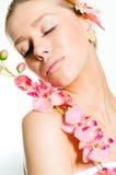 Κινηματογράφηση σε πρώτο πλάνο στην όμορφη νέα κυρία με το τέλειο δέρμα, τα κλειστά μάτια και το λουλούδι ορχιδεών εκμετάλλευσης  Στοκ φωτογραφία με δικαίωμα ελεύθερης χρήσης