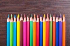 在棕色木表的多彩多姿的铅笔 免版税库存照片