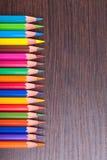 在棕色木表的多彩多姿的铅笔 免版税库存图片