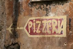薄饼在难看的东西墙壁上的餐馆标志 免版税库存照片